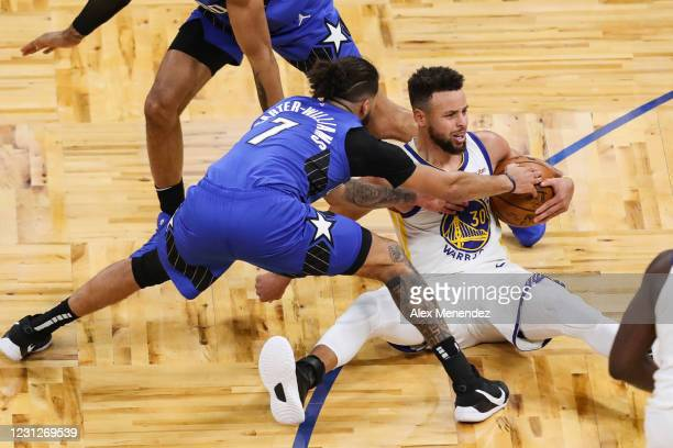 Michael Carter-Williams of the Orlando Magic and Stephen Curry of the Golden State Warriors fight for the ball during the first half at Amway Center...
