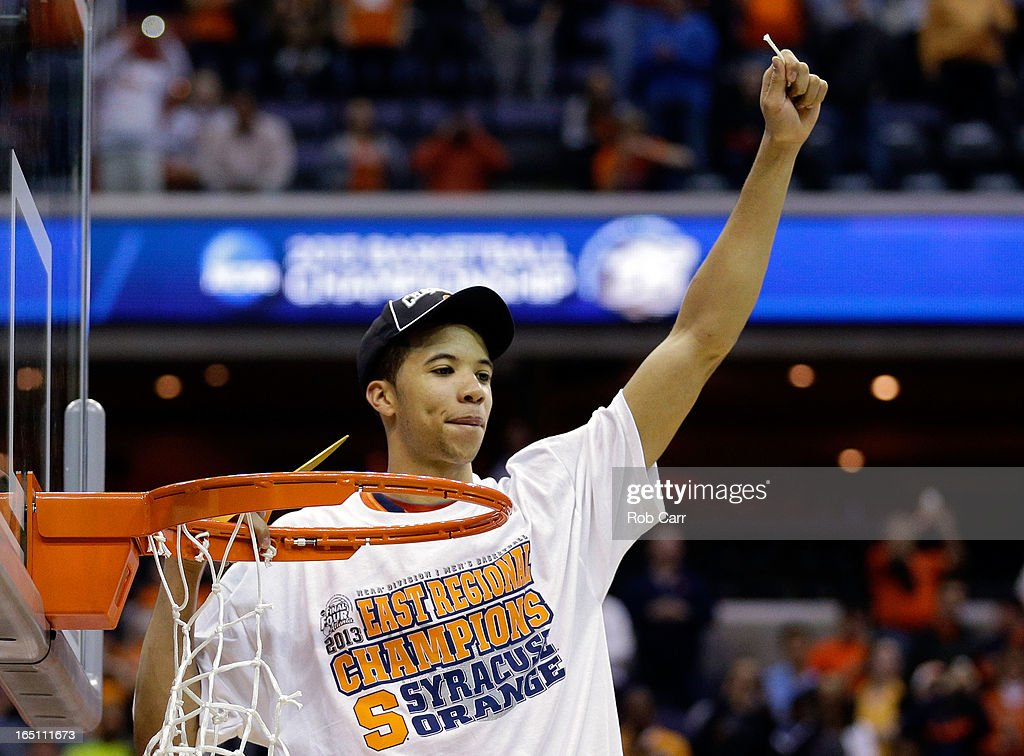 Michael Carter-Williams #1 of the Syracuse Orange cuts down the net after defeating the Marquette Golden Eagles to win the East Regional Round Final of the 2013 NCAA Men's Basketball Tournament at Verizon Center on March 30, 2013 in Washington, DC.