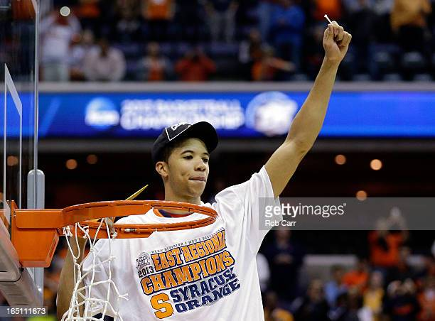 Michael CarterWilliams of the Syracuse Orange cuts down the net after defeating the Marquette Golden Eagles to win the East Regional Round Final of...
