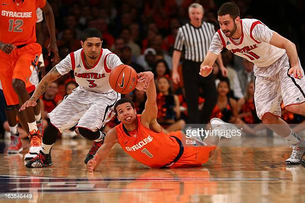 Michael CarterWilliams of the Syracuse Orange dives for a looseball against Peyton Siva and Luke Hancock of the Louisville Cardinals during the final...
