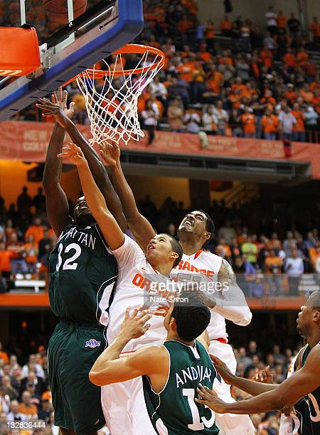 Michael CarterWilliams of the Syracuse Orange drives up to the basket with the help of teammate Fab Melo while being blocked by Rhamel Brown and Emmy...
