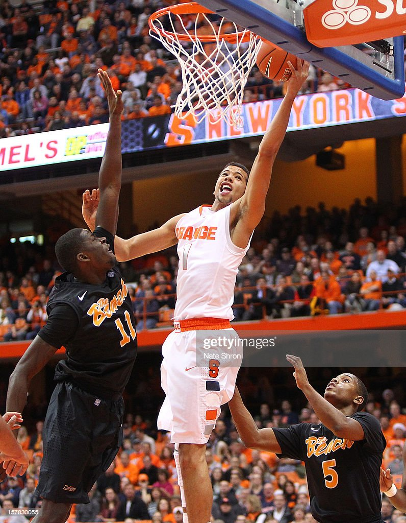 Michael Carter-Williams #1 of the Syracuse Orange puts the ball up to the basket against James Ennis #11 and Mike Caffey #5 of the Long Beach State 49ers during the game at the Carrier Dome on December 6, 2012 in Syracuse, New York.