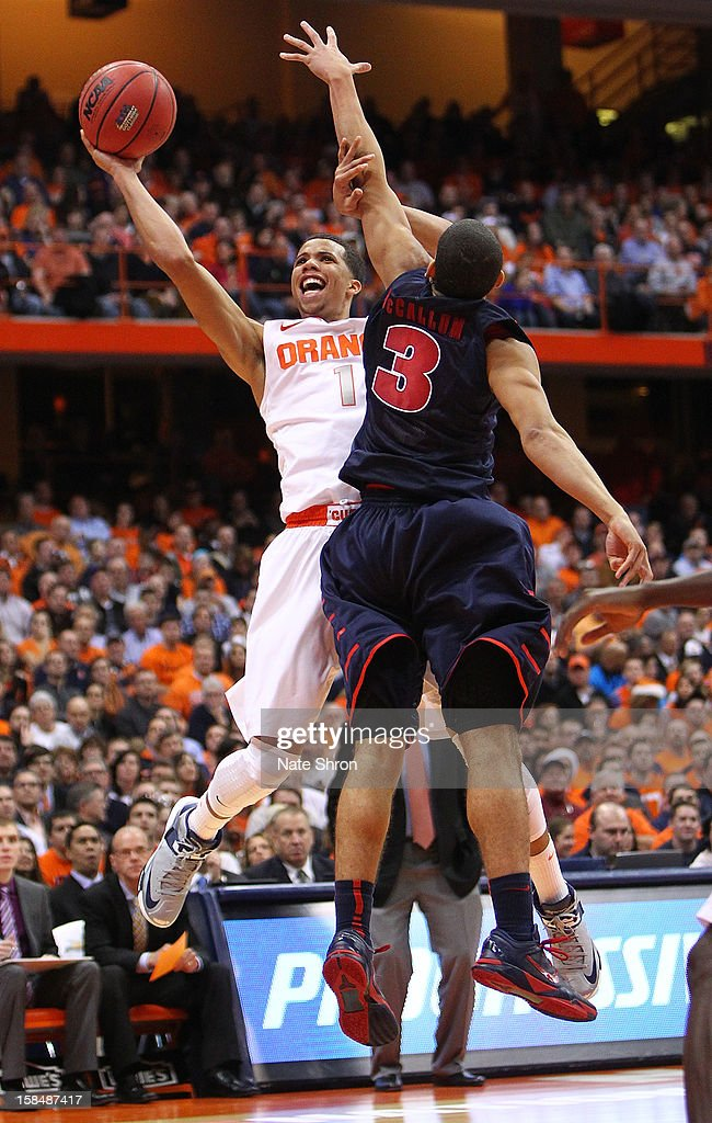 Michael Carter-Williams #1 of the Syracuse Orange puts the ball up to the basket against Ray McCallum #3 of the Detroit Titans during the game at the Carrier Dome on December 17, 2012 in Syracuse, New York.