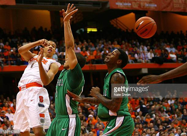 Michael CarterWilliams passes the ball for the Syracuse Orange against Dago Pena and Dennis Tinnon of the Marshall Thundering Herd during the game at...