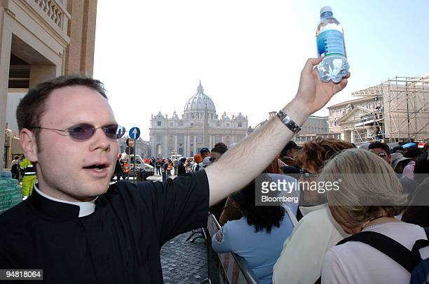 Michael Cassabon a priest working with the diocese of Charleston South Carolina passes out water to people as they wait in line to view the body of...