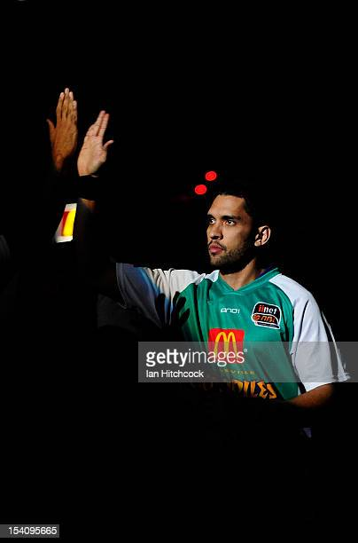 Michael Cedar of the Crocodiles greets his team mates after running onto the court before the start of the round two NBL match between the Townsville...