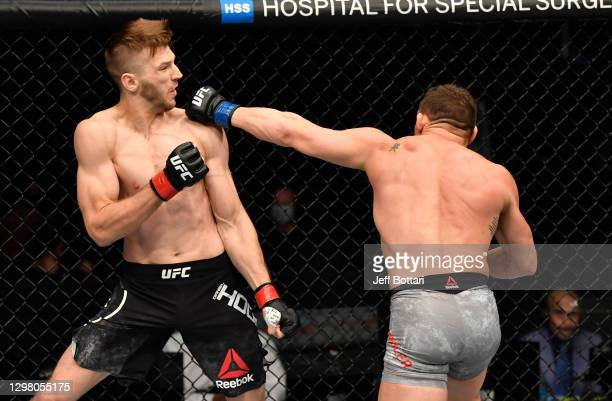 Michael Chandler punches Dan Hooker of New Zealand in a lightweight fight during the UFC 257 event inside Etihad Arena on UFC Fight Island on January...