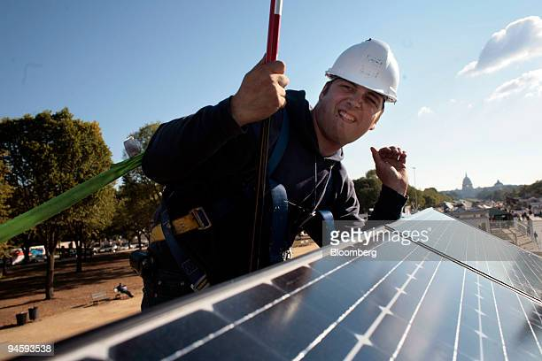 Michael Chapman of Ecole de Technologie Superieure in Montreal Canada cleans photovoltaic panels on the school's Lumin Essence solar house at the...