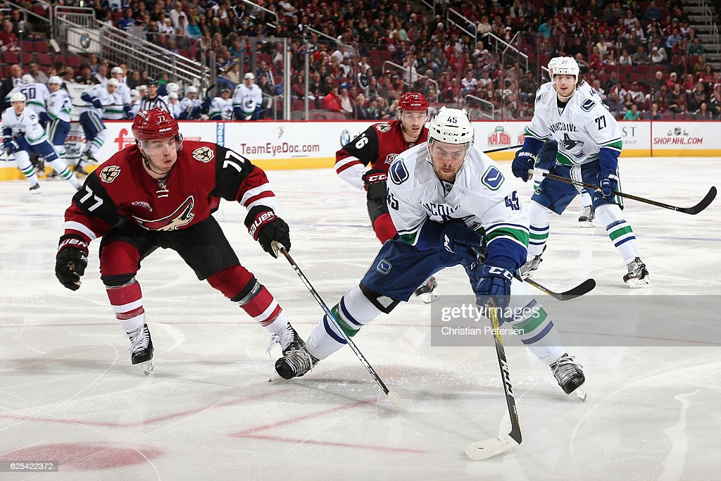 Michael Chaput #45 of the Vancouver Canucks skates with the puck ahead of Anthony DeAngelo #77 and Laurent Dauphin #76 of the Arizona Coyotes during the third period of the NHL game at Gila River Arena on November 23, 2016 in Glendale, Arizona.