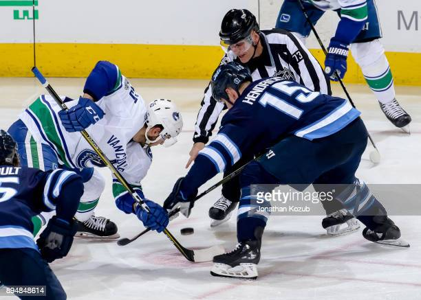 Michael Chaput of the Vancouver Canucks wins a third period faceoff against Matt Hendricks of the Winnipeg Jets at the Bell MTS Place on December 11...