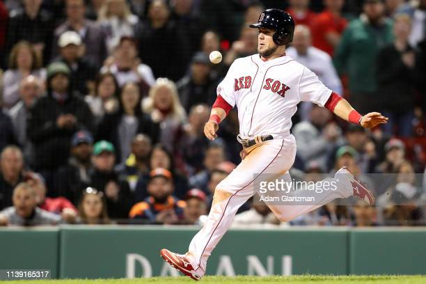 Michael Chavis of the Boston Red Sox betas the throw as he slides safely into home plate to score in the eighth inning of a game against the Detroit...