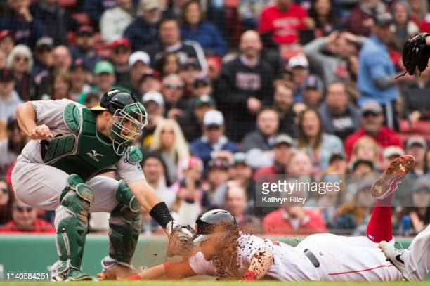 Michael Chavis of the Boston Red Sox is tagged out at home by Josh Phegley of Oakland Athletics in the second inning at Fenway Park on May 1 2019 in...