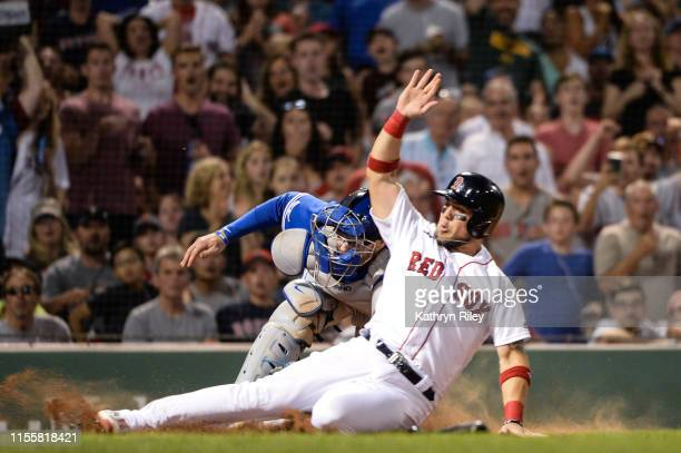Michael Chavis of the Boston Red Sox is tagged out at home plate by Danny Jansen of the Toronto Blue Jays in the sixth inning at Fenway Park on July...