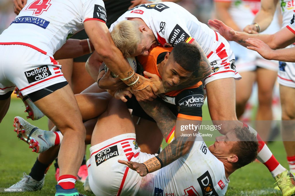 Michael Chee Kam of the Tigers is tackled by Gareth Widdop of the Dragons and Tariq Sims of the Dragons during the round 18 NRL match between the St George Illawarra Dragons and the Wests Tigers at UOW Jubilee Oval on July 15, 2018 in Sydney, Australia.