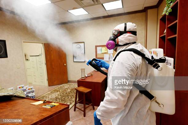 Michael Chiavola from Miracle Workers Cleaning Service wearing a full protective suit as a preventive measure against the coronavirus COVID19 sprays...