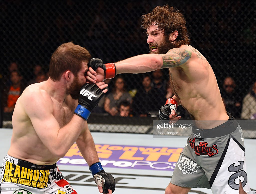 Michael Chiesa punches Mitch Clarke in their lightweight fight during the UFC Fight Night event at the Patriot Center on April 4, 2015 in Fairfax, Virginia.
