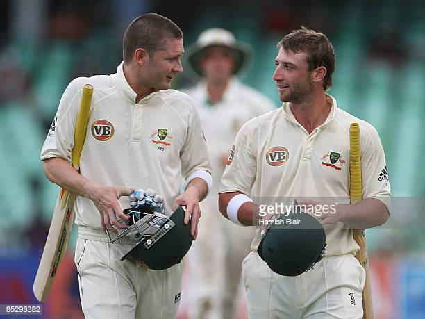 Michael Clarke and Phil Hughes of Australia leave the field at the close of play during day three of the Second Test between South Africa and...