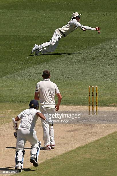 Michael Clarke of Australia fails to take a catch while diving with bowler Peter Siddle looking on as Mohammed Shami of India runs up the pitch after...