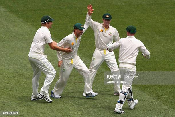 Michael Clarke of Australia is congratulated by team mates after taking a catch to dismiss Alastair Cook of England during day one of the Fourth...