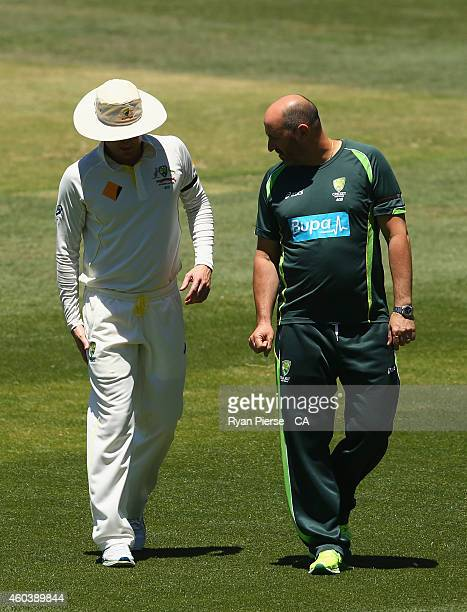 Michael Clarke of Australia leaves the ground with Alex Kountouris, Australian Team Physiotherapist, after he suffered an injury while fielding a...