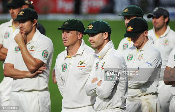 Michael Clarke of Australia looks dejected with team mates during the presentation on day five of the 5th Investec Ashes Test match between England...