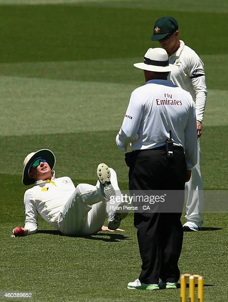 Michael Clarke of Australia pulls up while fielding a ball during day five of the First Test match between Australia and India at Adelaide Oval on...