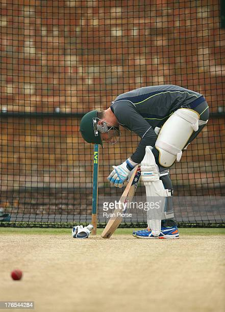 Michael Clarke of Australia takes off his glove after being struck on the hand while batting in the nets during an Australian Nets Session at The...