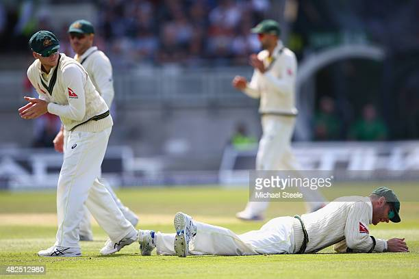 Michael Clarke the captain of Australia lies grounded after spilling a catch from Ian Bell at second slip off the bowling of Mitchell Starc during...