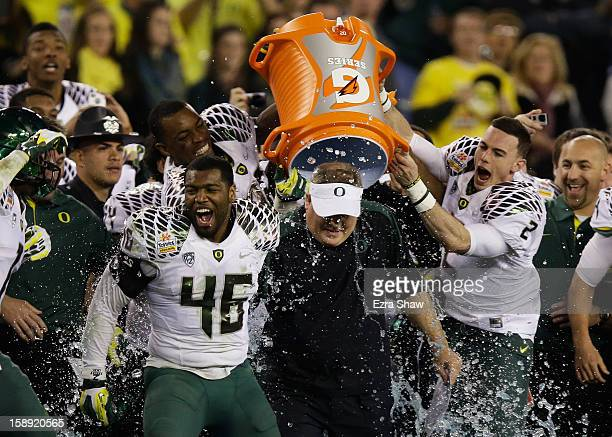 Michael Clay and Bryan Bennett dump the gatorade cooler on head coach Chip Kelly of the Oregon Ducks after their 35 to 17 victory over the Kansas...
