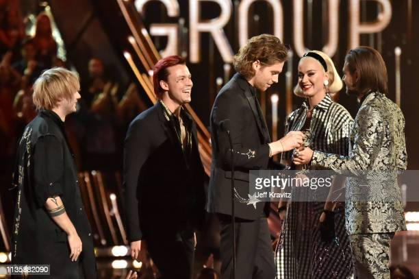 Michael Clifford Ashton Irwin and Luke Hemmings of 5 Seconds of Summer accept the Best Duo/Group of the Year award from Katy Perry and Zedd on stage...