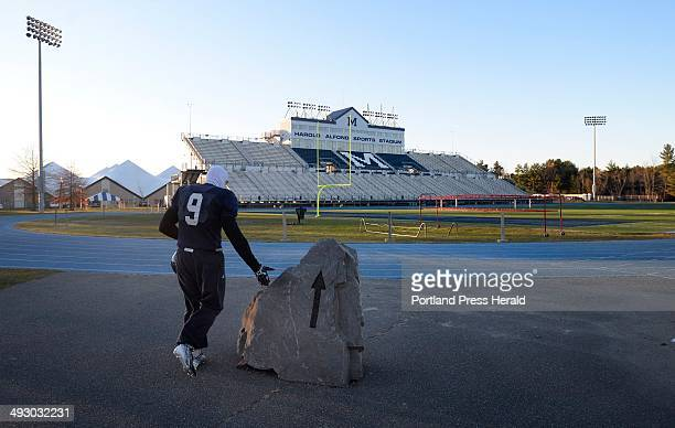 Michael Cole of the University of Maine football touches the rock at the entrance to the Harold Alfond Sports Stadium as he is the first player on...