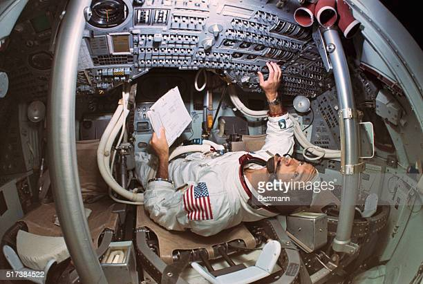 Michael Collins Apollo 11 command module pilot checks on technical material while in the Apollo Mission Simulator which inside is an exact model of...