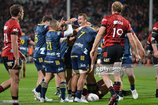 Michael Collins of the Highlanders is congratulated by team mates after scoring a try during the round 6 Super Rugby Aotearoa match between the...