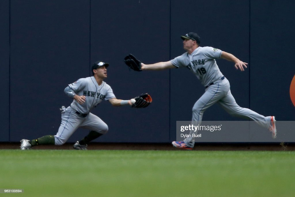 Michael Conforto #30 and Jay Bruce #19 of the New York Mets fail to catch a fly ball in the first inning against the Milwaukee Brewers at Miller Park on May 27, 2018 in Milwaukee, Wisconsin.