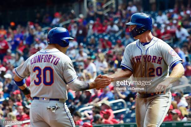 Michael Conforto and Pete Alonso of the New York Mets celebrate after scoring on an RBI double by Wilson Ramos in the first inning against the...