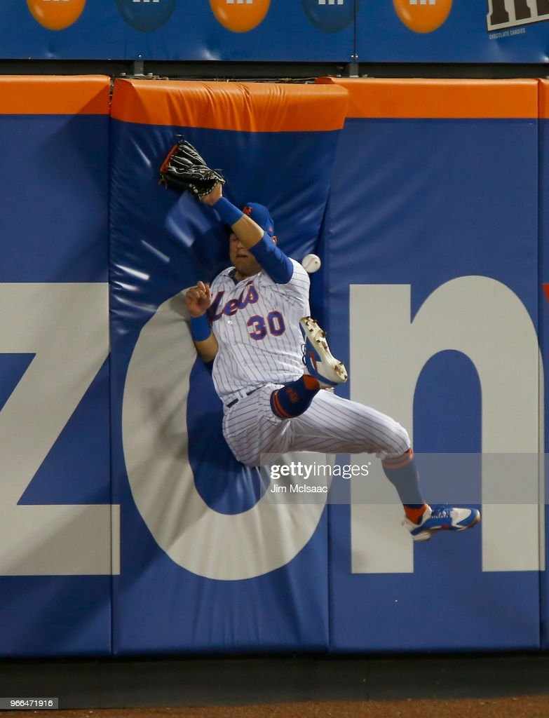 Michael Conforto #30 of the New York Mets can't come up with a ball hit in the seventh inning for a double by Jason Heyward of the Chicago Cubs at Citi Field on June 2, 2018 in the Flushing neighborhood of the Queens borough of New York City.
