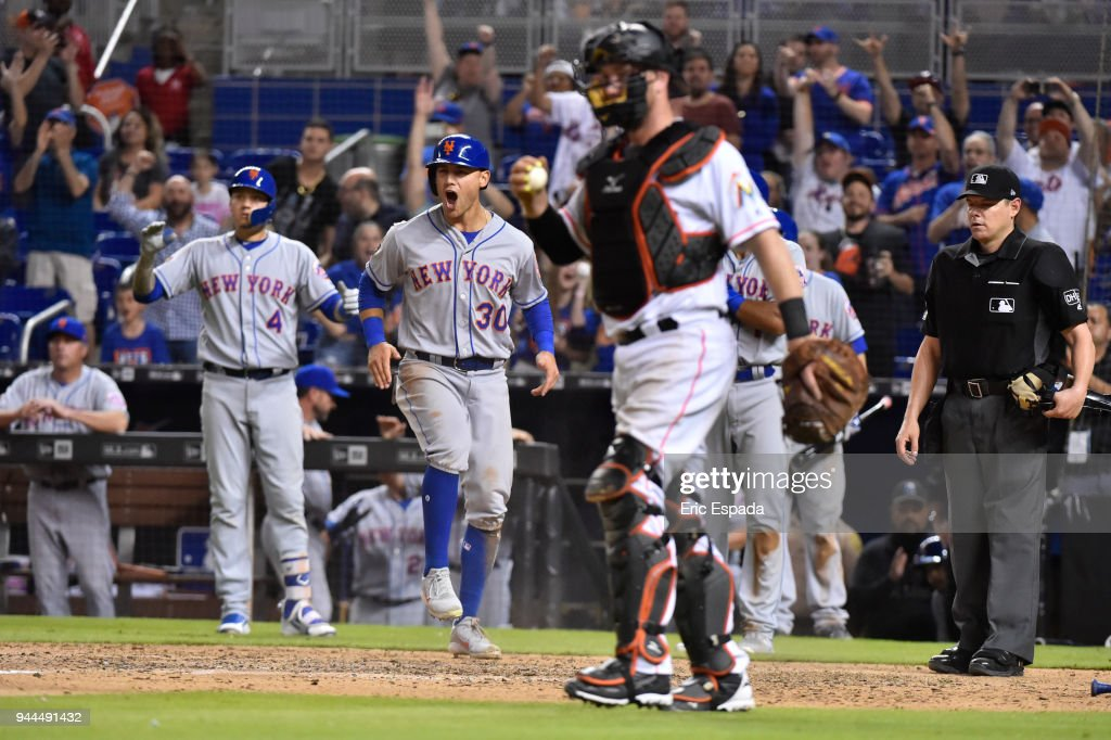 Michael Conforto #30 of the New York Mets celebrates after scoring on a double by Yoenis Cespedes #52 in the ninth inning against the Miami Marlins at Marlins Park on April 10, 2018 in Miami, Florida.