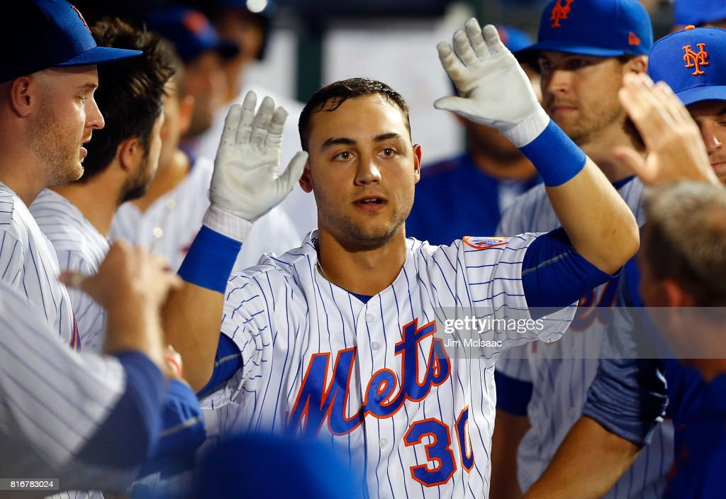 Michael Conforto #30 of the New York Mets celebrates his fifth inning home run against the St. Louis Cardinals in the dugout with his teammates on July 17, 2017 at Citi Field in the Flushing neighborhood of the Queens borough of New York City.