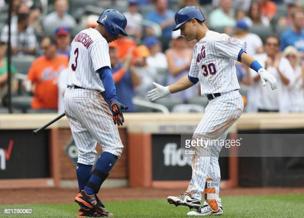 Michael Conforto of the New York Mets celebrates his solo home run with teammate Curtis Granderson in the third inning against the Oakland Athletics...