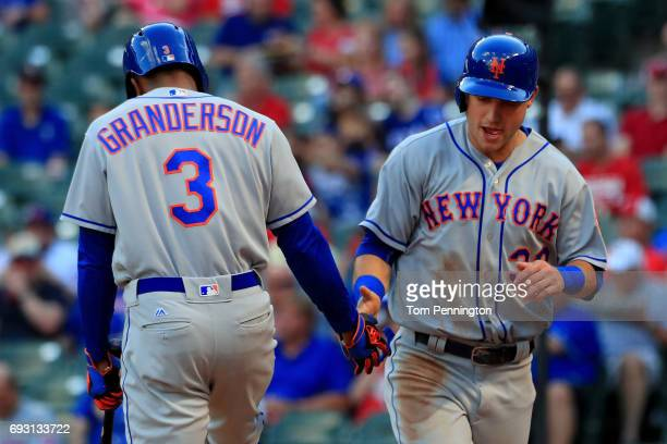 Michael Conforto of the New York Mets celebrates with Curtis Granderson of the New York Mets after scoring on a RBI single hit by Lucas Duda of the...