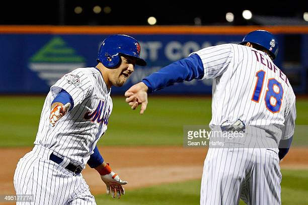 Michael Conforto of the New York Mets celebrates with third base coach Tim Teufel after hitting a solo home run in the third inning against the...