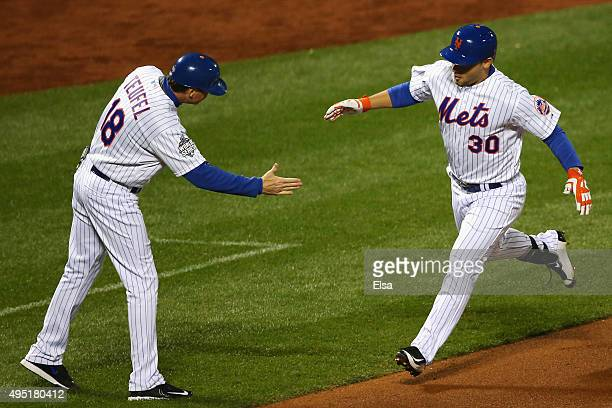 Michael Conforto of the New York Mets celebrates with third base coach Tim Teufel after hitting a solo home run in the fifth inning against the...