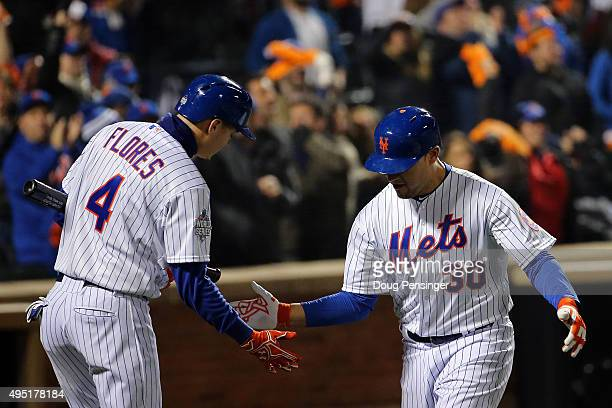 Michael Conforto of the New York Mets celebrateswith Wilmer Flores after hitting a solo home run in the third inning against the Kansas City Royals...
