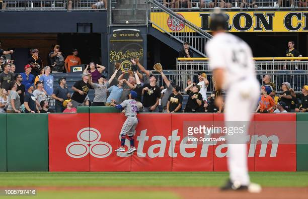 Michael Conforto of the New York Mets climbs the outfield wall as fans catch a two run home run off the bat of Josh Harrison of the Pittsburgh...