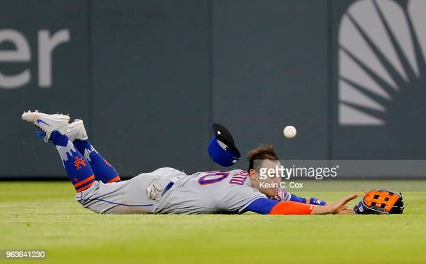Michael Conforto of the New York Mets dives but fails to catch a single hit by Dansby Swanson of the Atlanta Braves in the eighth inning at SunTrust...