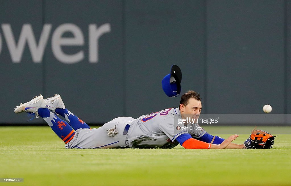 Michael Conforto #30 of the New York Mets dives but fails to catch a single hit by Dansby Swanson #7 of the Atlanta Braves in the eighth inning at SunTrust Park on May 29, 2018 in Atlanta, Georgia.