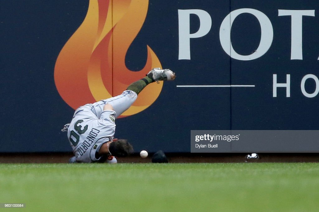 Michael Conforto #30 of the New York Mets fails to catch a fly ball in the first inning against the Milwaukee Brewers at Miller Park on May 27, 2018 in Milwaukee, Wisconsin.