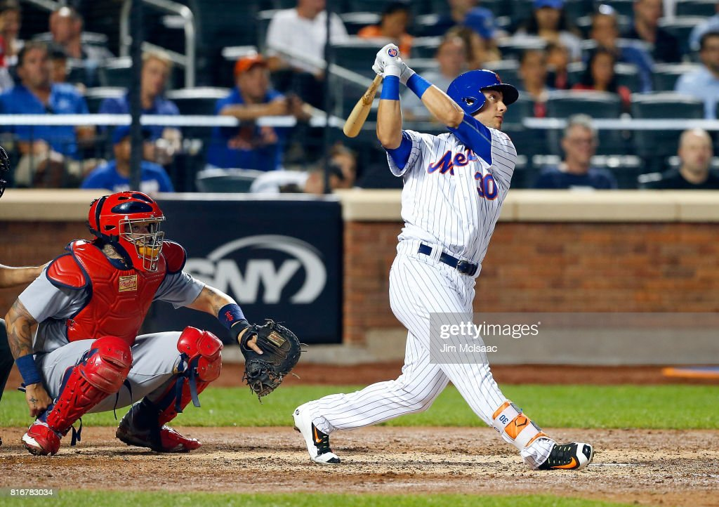 Michael Conforto #30 of the New York Mets follows through on a fifth inning home run as Yadier Molina #4 of the St. Louis Cardinals looks on at Citi Field on July 17, 2017 in the Flushing neighborhood of the Queens borough of New York City.