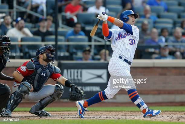Michael Conforto of the New York Mets follows through on a fifth inning three run home run against the Washington Nationals at Citi Field on July 14...