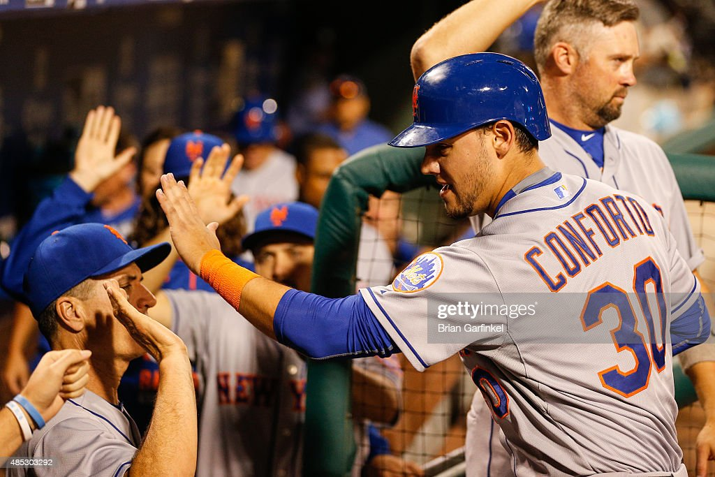 Michael Conforto #30 of the New York Mets high-fives teammates in the dugout after scoring a run in the sixth inning of the game against the Philadelphia Phillies at Citizens Bank Park on August 26, 2015 in Philadelphia, Pennsylvania. The Mets won 9-4.